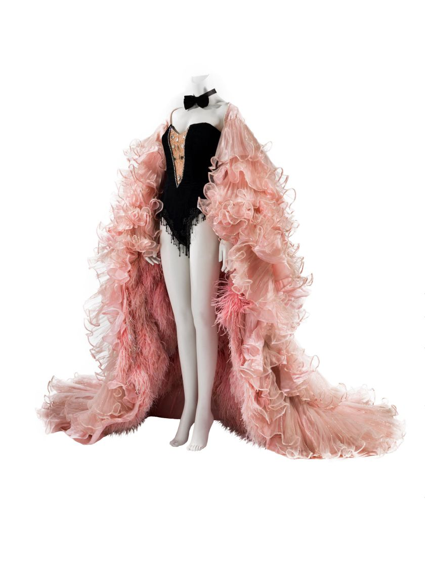 Tenue dessinée par Michel Fresnay et réalisées par Mine barral Vergès. Tenue de scène 1980. Cape en plumes d'autruche et body en velours noir. Collection Palais Galliera © Julien Vidal / Galliera /