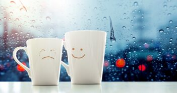 ©Encouragement concept, Friend of Coffee Mug with Sadness crying face cartoon and kindness happy face inside the room, Blurred city lights and rain drop in city as outside view through glass window |- Ayez le courage d'être gentils